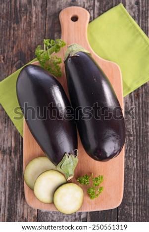 raw eggplant on board - stock photo