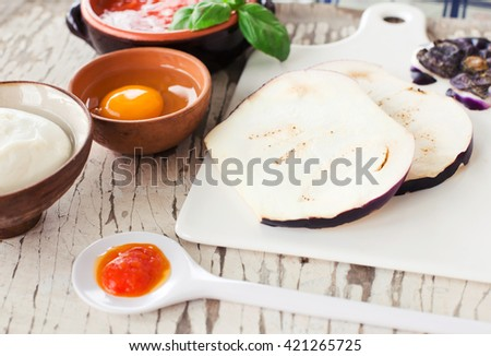 raw eggplants and ingredients for parmigiana