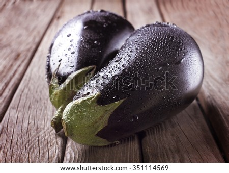 Raw eggplants with water drops on wooden table - stock photo