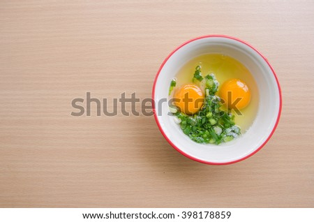 Raw eggs and onions In a bowl on wooden table.Lift copy space. - stock photo