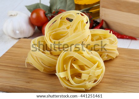 Raw fettuccine pasta on the wood backgroud ready for cooking