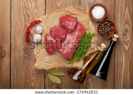 Raw fillet beef steak and spices on wooden table. Top view - stock photo