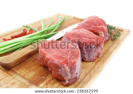 raw fillet chops : fresh beef meat with thyme and red hot dry pepper on wooden plate . isolated over white background - stock photo
