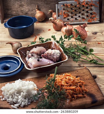raw fillet of chicken meat and onions in the process of cooking food - stock photo