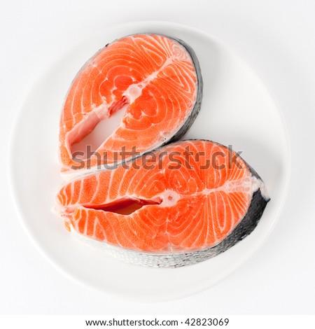 Raw fillet of fresh salmon fish on white plate - stock photo