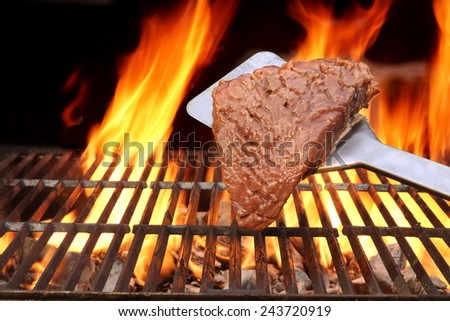 Raw Fillet Steak on the Spatula. Flaming BBQ Grill in the Background - stock photo