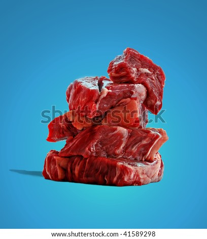 Raw fillet steaks isolated on blue background - stock photo