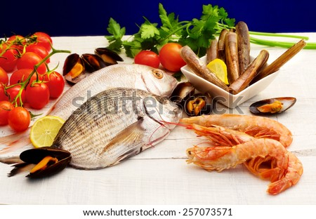 raw fish and mollusk selection over white wood - stock photo