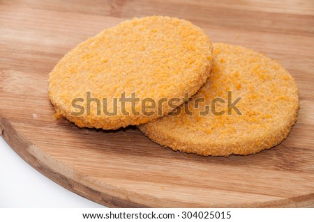 Raw fish burgers on a wooden board. - stock photo