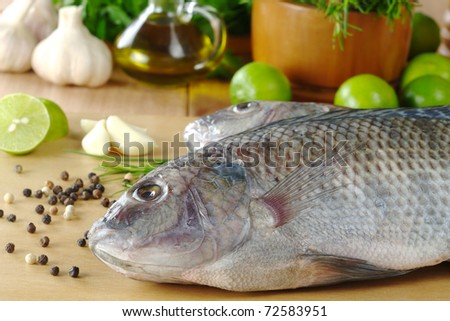 """Raw fish called """"tilapia"""" surrounded by spices, herbs and seasonings (Selective Focus, Focus on the head and the belly part of the fish) - stock photo"""