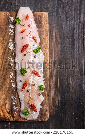 raw Fish fillet with herbs and spices on cutting board , top view - stock photo