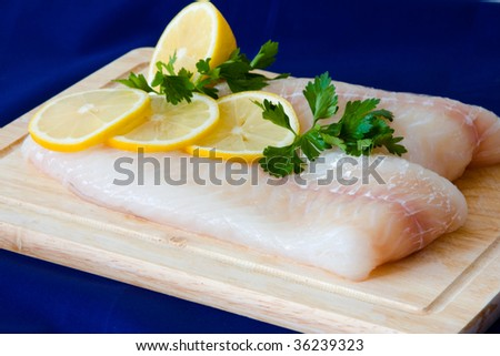 Raw fish fillet with punch and lemons - stock photo