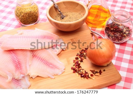 Raw fish tlapia on cutting board surrounded by spices, herbs and seasonings, selective focus - stock photo
