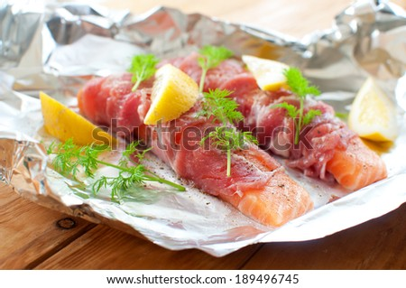 Raw fish wrapped with bacon - stock photo