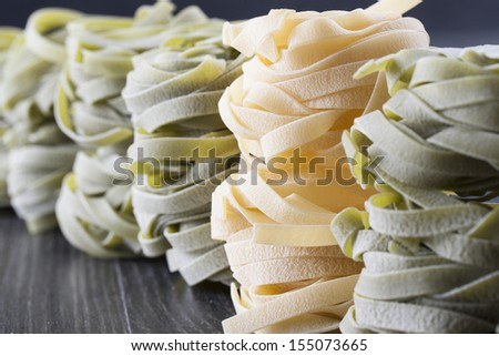 Raw food composition - yellow and green tagliatelle pasta on a dark background.