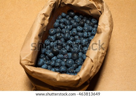 Raw food concept. Box with fresh blueberries packed in ecological material - paper - on wooden background. Close up. Vintage style. Studio shot