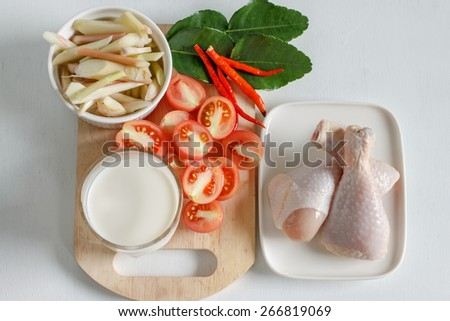 "Raw food: ingredients for ""Tom kha gai"" or Coconut milk soup with Chicken put on white wood table. Popular Thai food from top view. - stock photo"