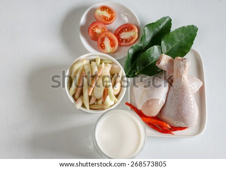 """Raw food: ingredients for """"Tom kha gai"""" or Coconut milk soup with Chicken put on white wood table. Popular Thai food from top view. - stock photo"""