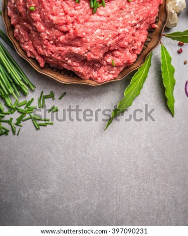 Raw force meat and fresh green seasoning ingredients for tasty cooking on stone background, top view, border - stock photo