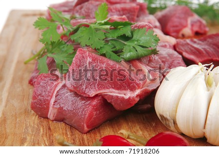 raw fresh beef meat fillet on a wooden plate with dill , hot green red peppers isolated over white background - stock photo