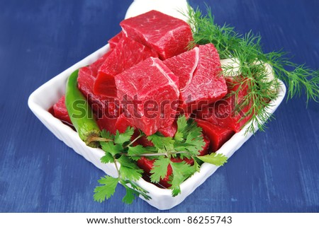 raw fresh beef meat slices in a white bowls with dill and green hot peppers serving over blue wooden table - stock photo