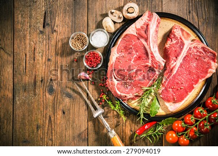 Raw fresh beef steaks and seasoning on wooden background - stock photo