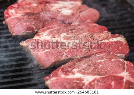 Raw fresh beef steaks being fried or prepared on grill or BBQ with pepper, spices and seasoning - stock photo