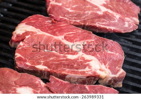 Raw fresh beef steaks being fryed or prepared on grill or BBQ