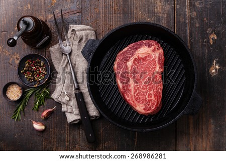 Raw fresh Black Angus Steak on grill pan on wooden background - stock photo