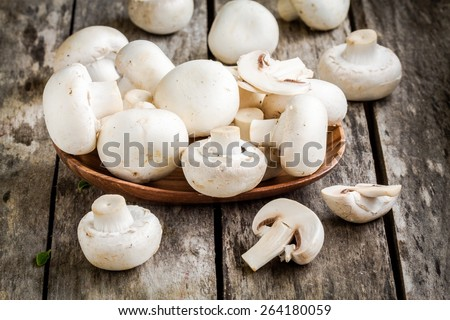 raw fresh champignons in  the wooden bowl on rustic table - stock photo