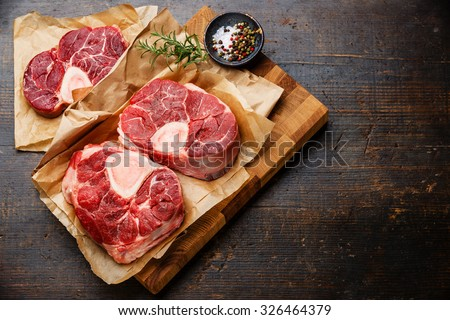 Raw fresh cross cut veal shank and seasonings for making Osso Buco on wooden cutting board  - stock photo