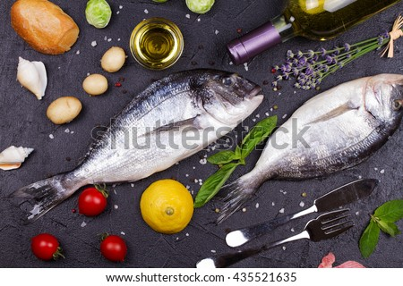 Raw fresh dorado fish with brussels sprouts, tomatoes, lemon, young potato, greens, bread, white wine bottle and olive oil on dark background. View from above, top studio shot