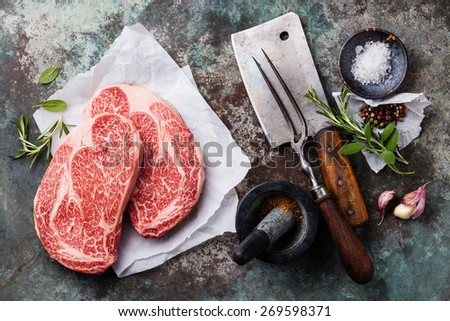 Raw fresh marbled meat Black Angus Steak and seasonings on metal background - stock photo