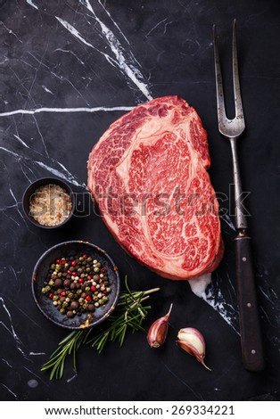 Raw fresh marbled meat Black Angus Steak Ribeye, seasonings and meat fork on dark marble background  - stock photo