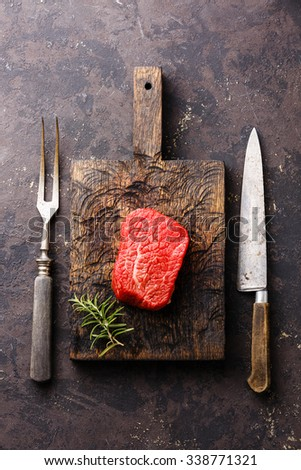 Raw fresh marbled meat Steak on meat cutting board and meat fork and kitchen knife on dark background - stock photo