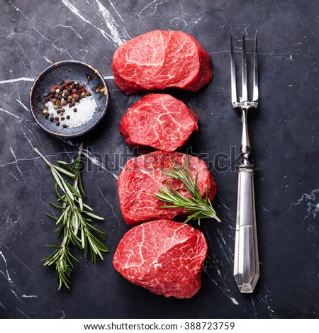 Raw fresh marbled meat Steak, seasonings and meat fork on dark marble background  - stock photo