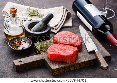 Raw fresh marbled meat Steaks with seasonings and bottle of red wine on dark background - stock photo