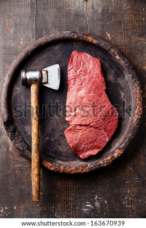 Raw fresh meat and meat cleaver on dark background - stock photo