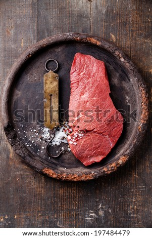 Raw fresh meat and vintage steelyard on dark background - stock photo