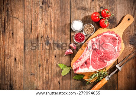 Raw fresh meat rib eye steak and seasoning on wooden background - stock photo