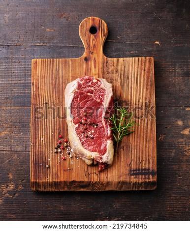 Raw fresh meat Ribeye Steak and seasoning on dark background - stock photo