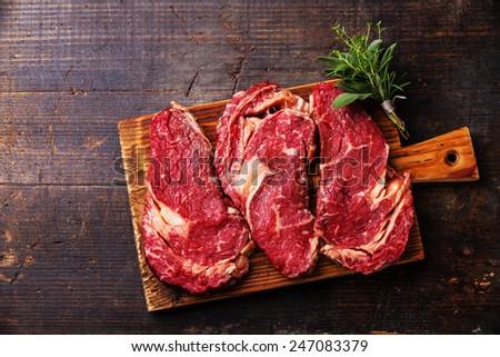 Raw fresh meat Ribeye steak entrecote on dark wooden background  - stock photo