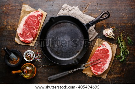 Raw fresh meat Steak Striploin for two with condiments around iron frying pan - stock photo