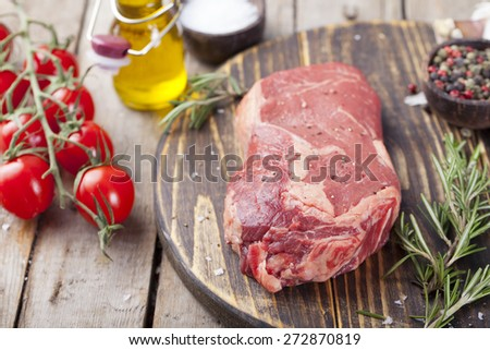Raw fresh meat  Steak with salt and pepper , rosemary and tomatoes on cutting board on dark wooden background - stock photo