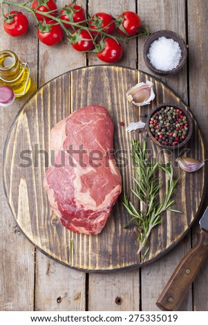 Raw fresh meat Steak with salt and pepper , rosemary and tomatoes on cutting board on dark wooden background. copy space - stock photo