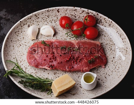 Raw fresh meat Striploin steak and seasoning on a spotted plate over dark metal background, top view - stock photo