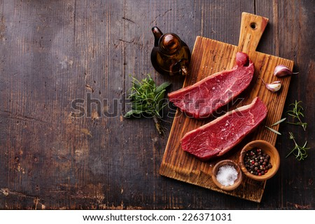 Raw fresh meat Striploin steak and seasoning on dark wooden background - stock photo