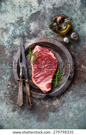 Raw fresh meat Striploin steak and seasoning on metal background - stock photo
