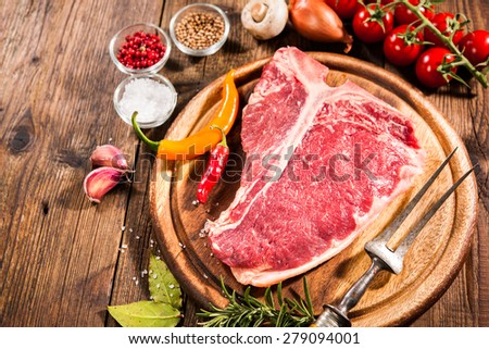 Raw fresh meat t-bone steak and seasoning on wooden background - stock photo