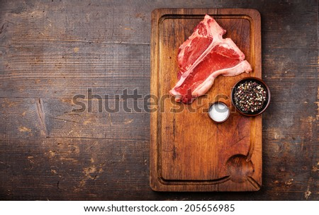 Raw fresh meat T-Bone Steak with salt and pepper on cutting board on dark wooden background - stock photo
